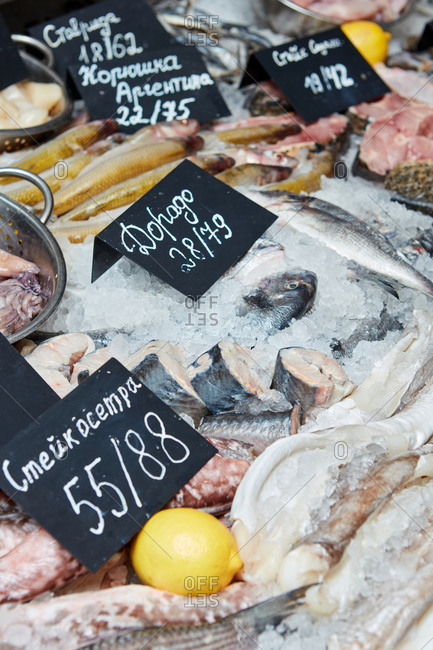 Supermarket counter with fresh cooled fish smelt, dorado, sturgeon steaks on ice with price tags. Selling Healthy Seafood.
