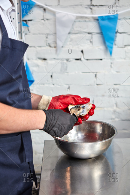 A man in a black apron opens a shell of oysters on a metal surface around a white brick wall. Cooking gourmet health food