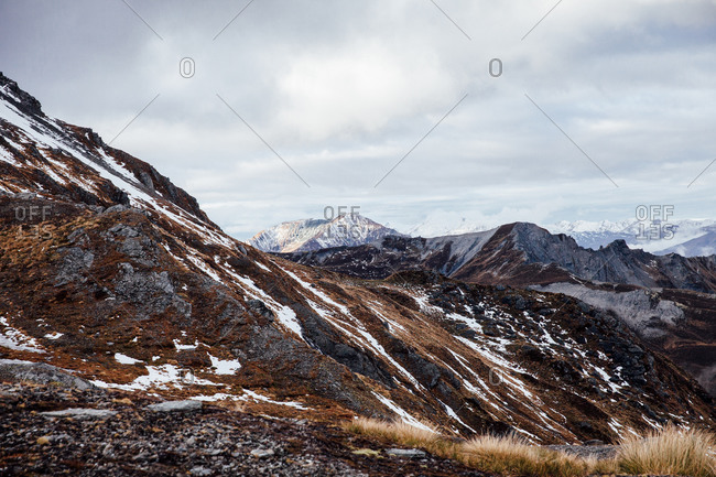Snowy mountain range under cloudy skies