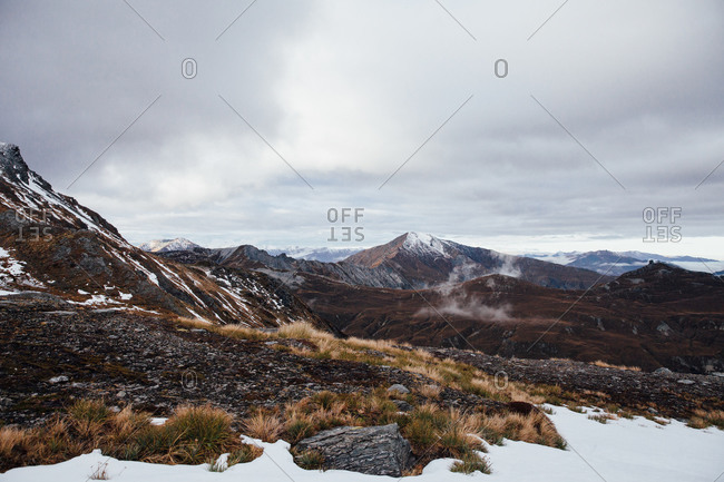 Mountain range with patches of snow under cloudy skies