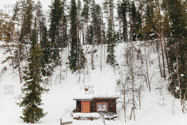 A rustic cottage on a snowy hill in rural Finland