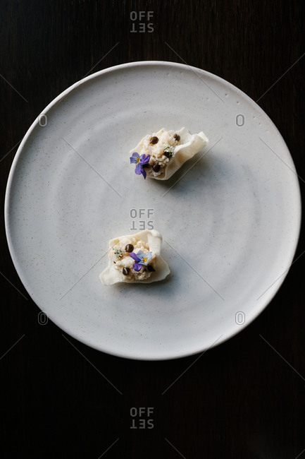 Overhead view of a gourmet dessert with edible flowers