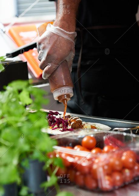A man adding chili sauce to a tortilla inside a food truck