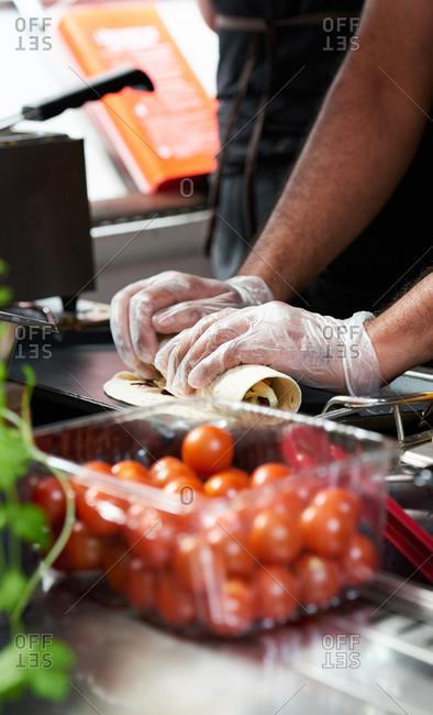 A man rolling flour tortillas inside a food truck