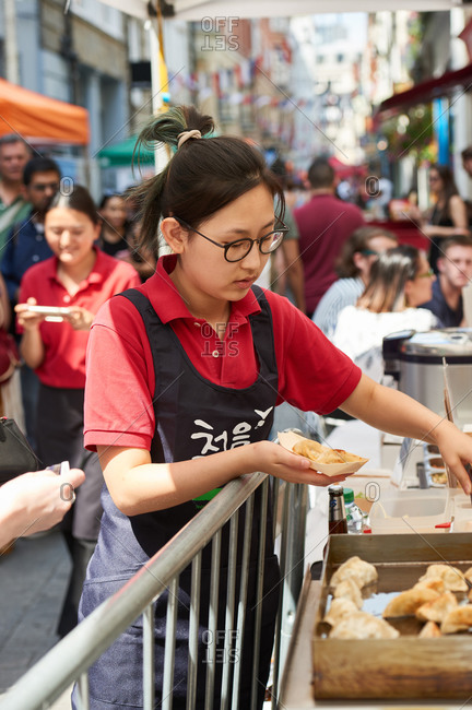 London, United Kingdom - July 23, 2016: A young woman serving Japanese gyoza dumplings at a street food market
