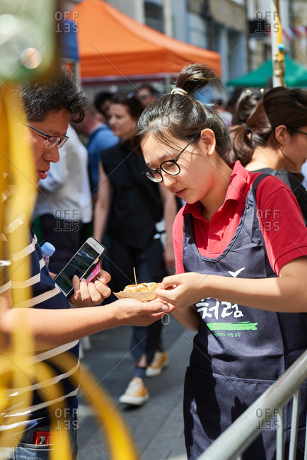 London, United Kingdom - July 23, 2016: A customer paying a young woman at a street food market