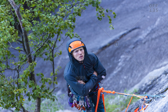 Man being bored belaying climber while hanging from granite wall cold