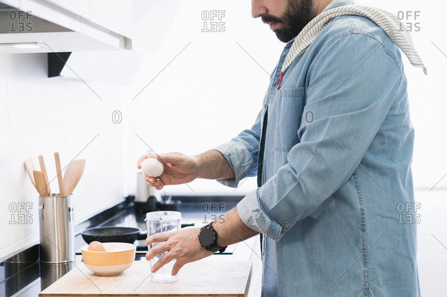 Man cooking in the kitchen in a denim shirt. An anonymous man is going to crack an egg