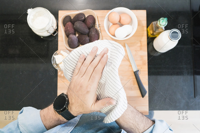 Man cooking in the kitchen in a denim shirt. An anonymous man is cleaning his hands
