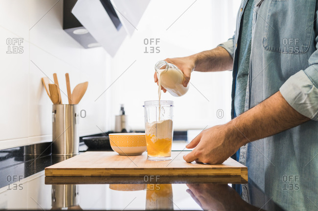 Man cooking in the kitchen in a denim shirt. An anonymous man is pouring milk into a container