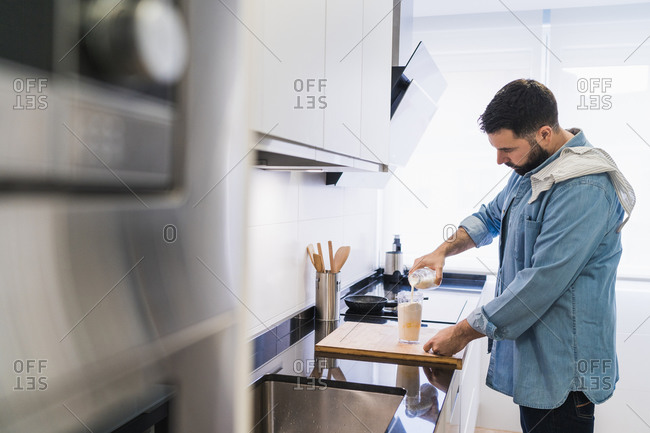 Man cooking in the kitchen in a denim shirt. A man is pouring milk into a container