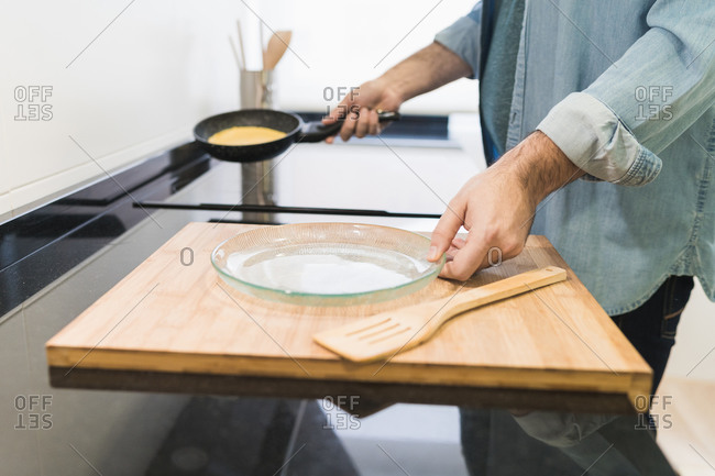 Man cooking in the kitchen in a denim shirt. an anonymous man is holding a pan with a pancake to put it on a plate
