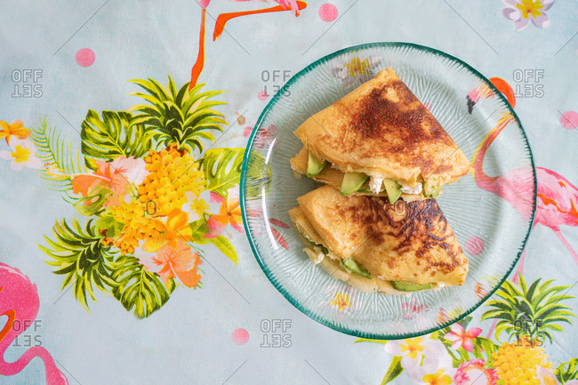 A plate of pancakes with cheese and avocado is on the table with a colorful tablecloth