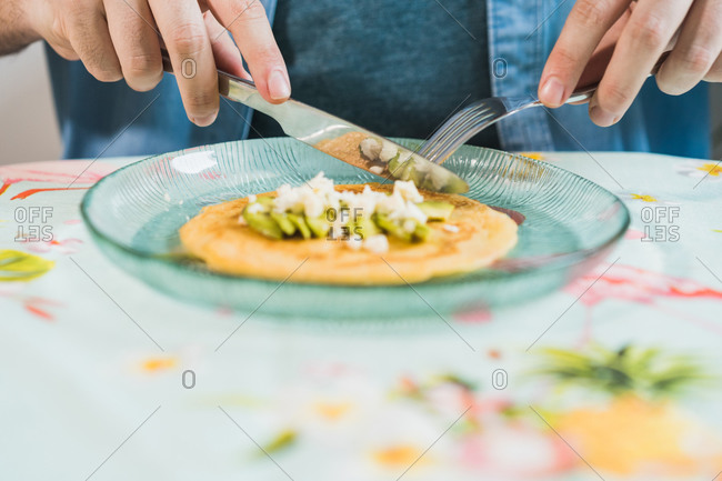 A plate of pancakes with cheese and avocado is on the table. An anonymous man is eating with a colorful tablecloth