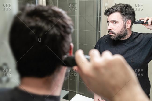 Self haircut. A man is cutting his hair with a hair clipper in the bathroom