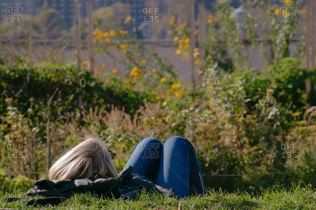 Young woman relaxing in a park on a sunny day in Brooklyn, New York