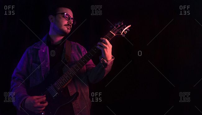 Young adult plays electric guitar under colored lights