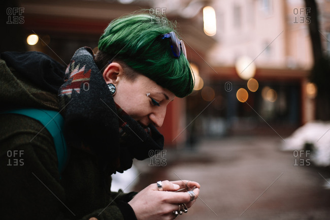 Portrait of happy non-binary hipster woman using smart phone in city