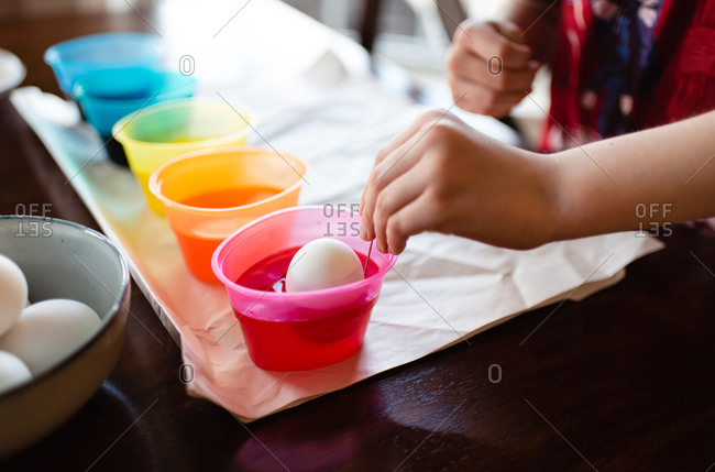 Close up of a child's hand dying an egg for Easter decoration.