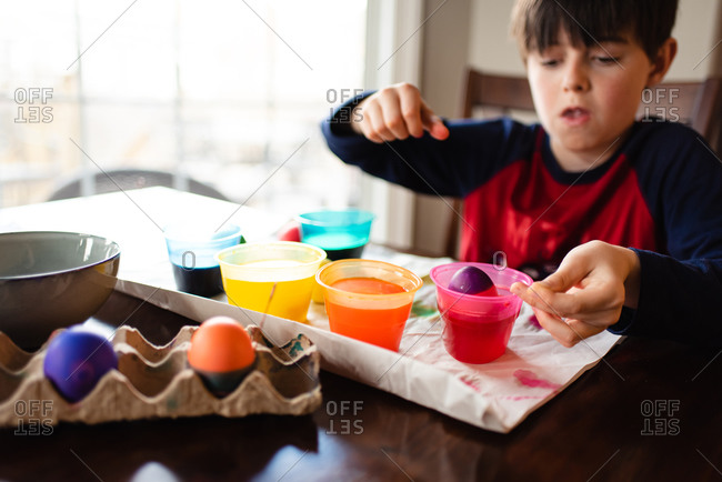 Boy dipping an egg into a bowl of dye to color it for Easter.