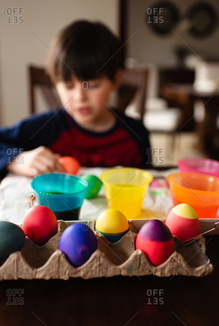 Colorful Easter eggs with boy dying them in the background.