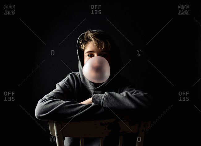 Teen boy in hoodie sitting on a chair in dark room blowing a bubble.