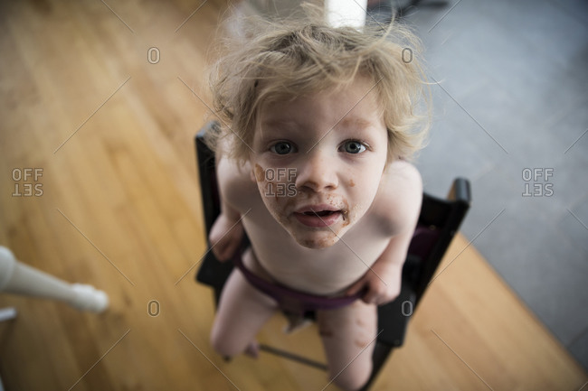 Messy Faced Toddler Sits in High Chair and Looks Up Into Camera