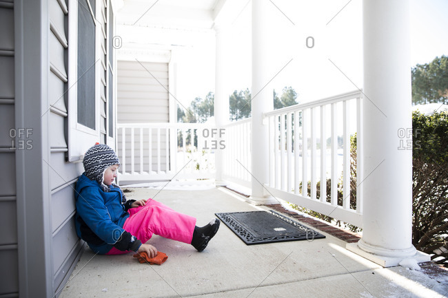 Wide View of Boy in Pink Snow Pants Sitting on Snowy Front Porch