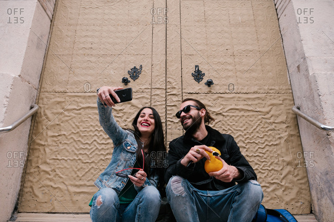 Man and woman smiling, making a selfie sitting in the city