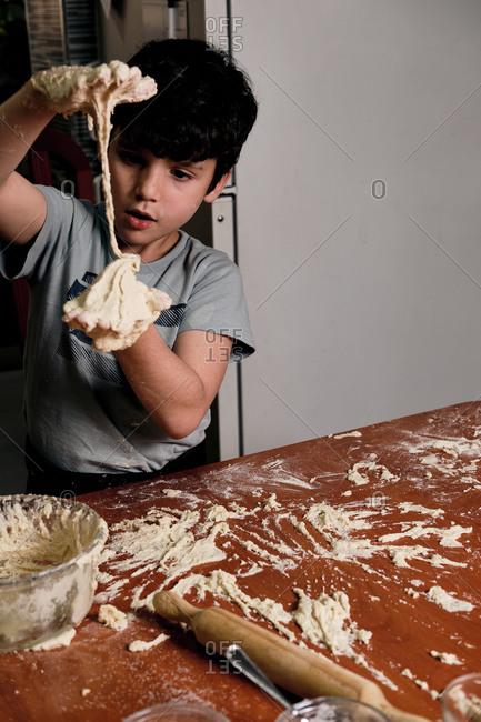 Child preparing pizza dough to make at home