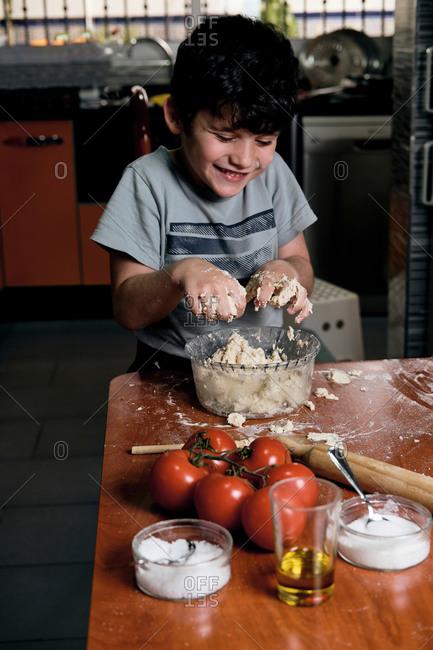 Child preparing pizza dough at home