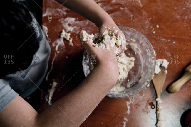 Child preparing pizza dough at home, top view