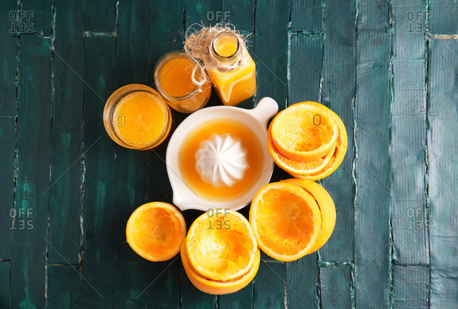 Still life of a green wooden base of an orange squeezer with orange juice
