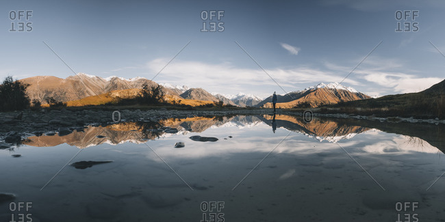 Panorama of a young woman standing in front of puddle, Canterbury, NZ