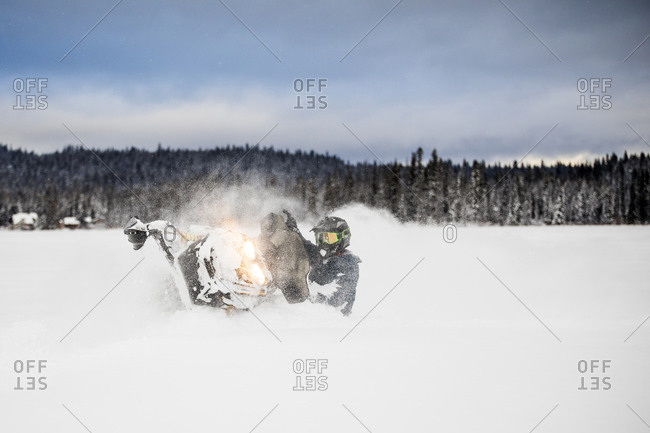Confident and aggressive rider operates snowmobile in deep snow.