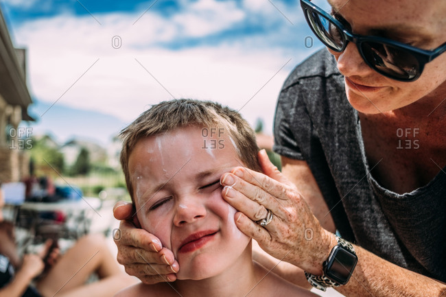 Close up of mother putting lotion on son\'s face at pool on summer day
