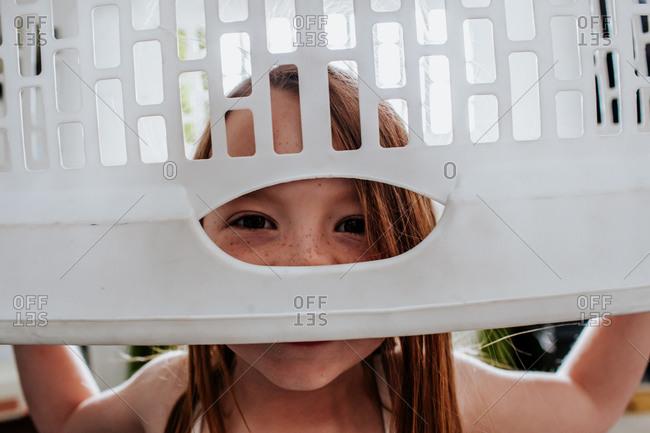 Goofy cute child peeking through laundry basket