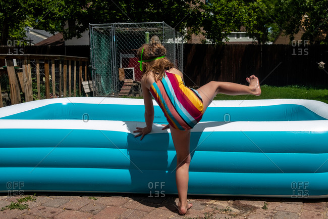 Straight on shot of young girl getting into small pool