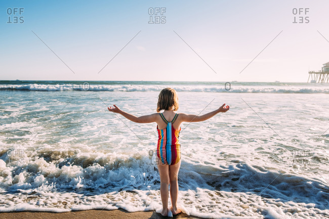 Young girl standing at waters edge on beach, facing ocean