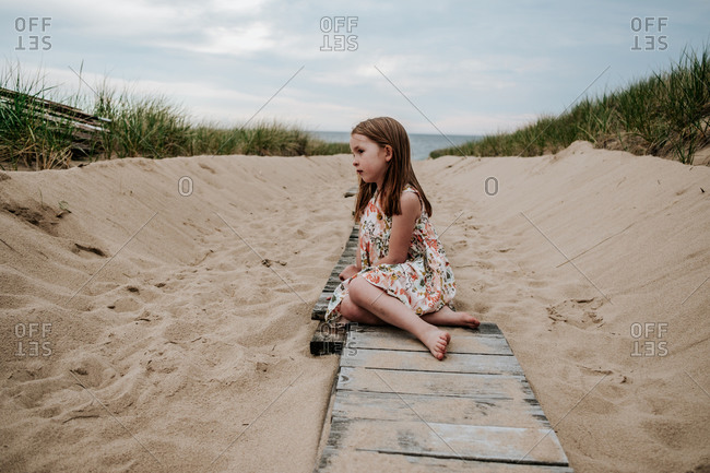 Young girl sitting on pathway going out to Lake Michigan