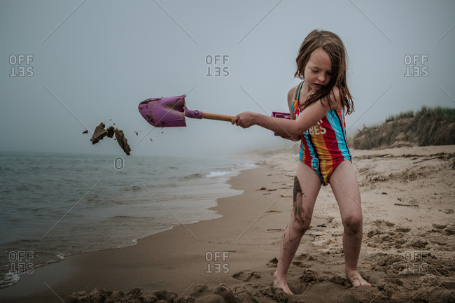Young girl digging in sand on beach on cloudy day