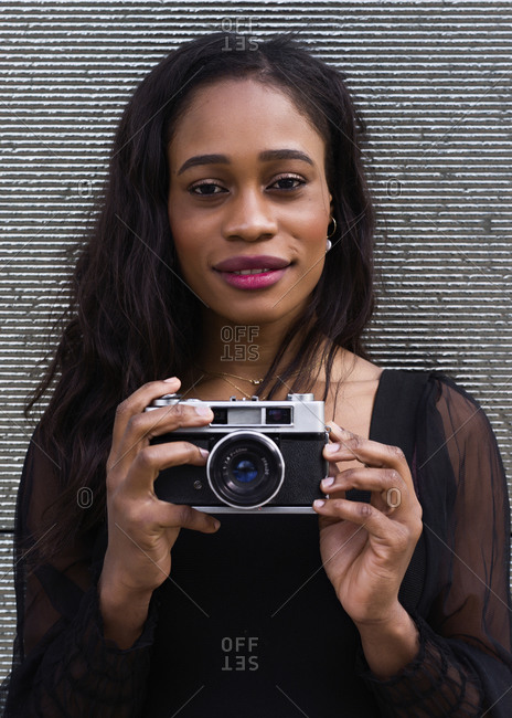 Head portrait of a young African-American woman posing with a camera