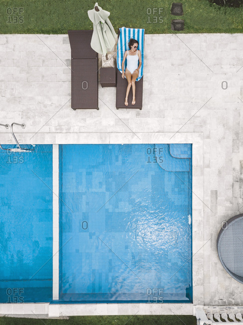 Aerial view of attractive woman near the pool at resort