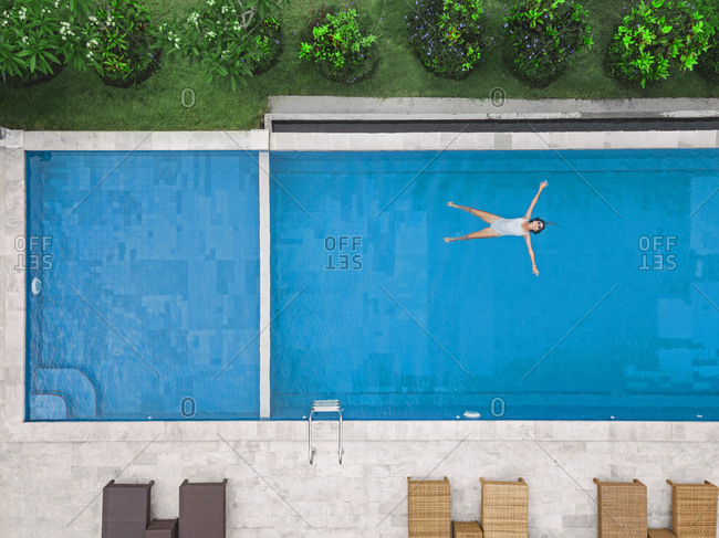 Aerial view of attractive woman floating over water at resort