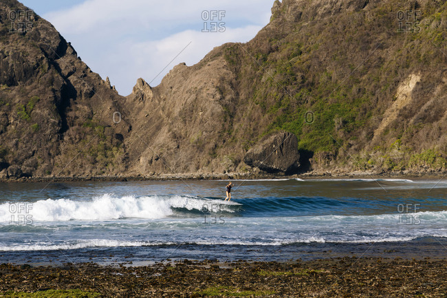 Female surfer on a wave, Sumbawa, Indonesia
