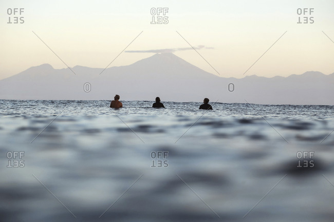 Surfers on surfboard on the sea waiting for a wave, Volcano Rinjani