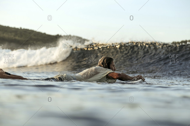 Surfer in sea at sunset, Lombok, Indonesia