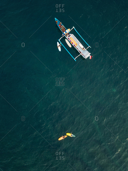 Aerial view of surfers and boat in the ocean, Lombok, Indonesia