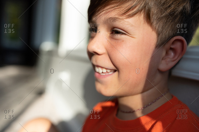 Smiling close up profile of boy siting next to window inside