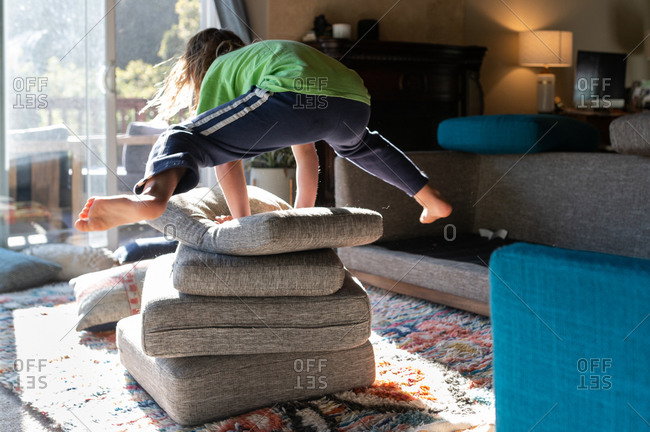 Child jumping over a pile of couch cushion pillows in living room
